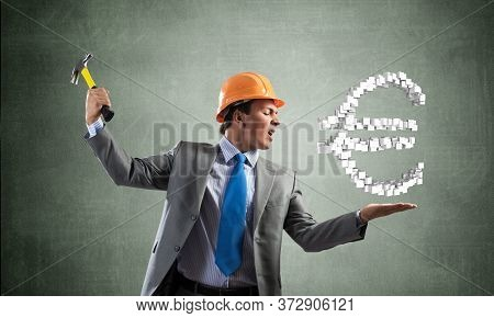 Furious Businessman Going To Crash With Hammer Euro Currency Sign. Handsome Man In Business Suit And