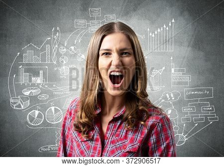 Frenzied Young Woman Screaming With Anger. Financial Charts And Business Doodles On Grey Wall. Emoti