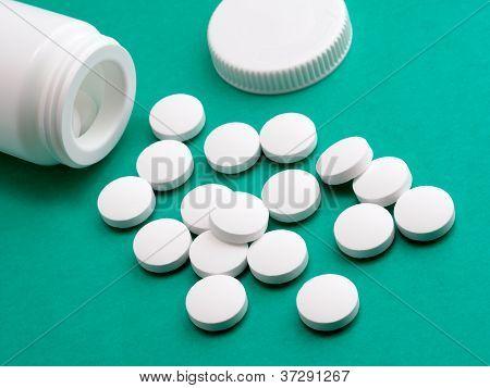 Pill From Prescription Bottle On Green Background