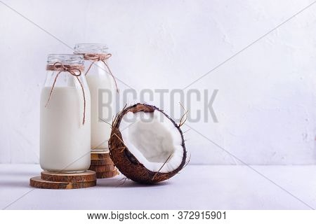 Two Glass Bottles Of Coconut Vegan Milk On Wooden Coasters With Chopped Brown Coconut On A White Bac