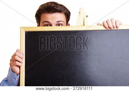 Manager with stage fright is hiding behind a blackboard