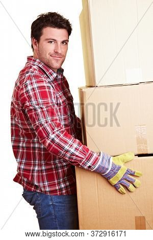 Smiling moving assistant carries a lot of moving boxes