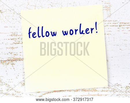 Concept Of Reminder About Fellow Worker. Yellow Sticky Sheet Of Paper On Wooden Wall With Inscriptio