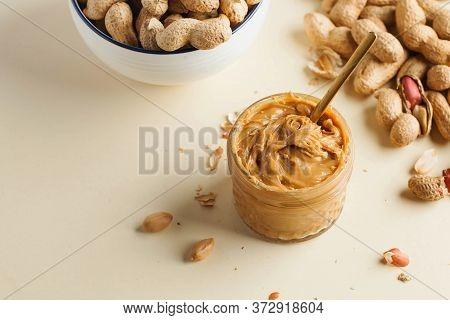 Closeup Peanut Butter In A Glass Jar, A Handful Of Peanuts In Shell. Foodphoto. Copy Space. Breakfas