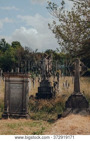 London, Uk - June 16, 2020: Angel Statue On A Tomb Amongst Tombstones Inside Hampstead Cemetery, A H