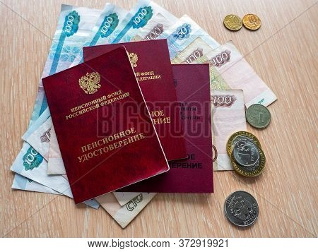 Three Pension Certificates Lie On Russian Money. Near Metal Ruble Coins. Receiving And Distribution