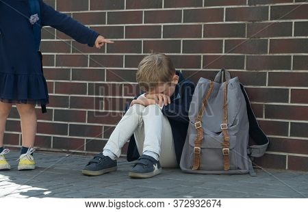 School Bully. Kid Boy Sitting Near Wall And Cry Because Of Bullying