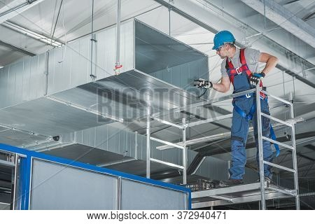 Caucasian Hvac Technician Worker In His 40s Testing Newly Installed Warehouse Ventilation System. Co