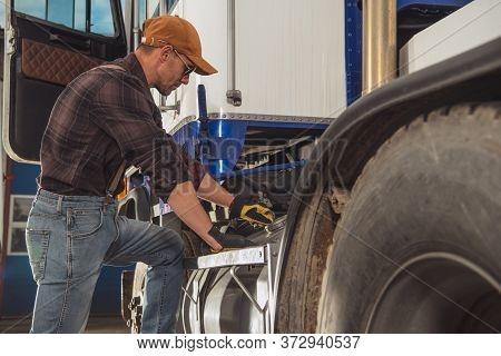 Heavy Duty Commercial Transportation Theme. Caucasian Trucker In His 40s Looking Inside Semi Truck F