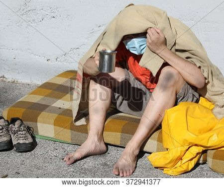 Vagabond With Surgical Mask Asks Pedestrians For Alms On A Mattress On The City Sidewalk