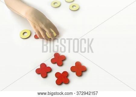 Kid Tic-tac-toe Wood Board Game On White Background. Children's Hand Holds A Toe. Developmental Game