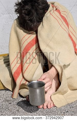 Desperate Young Homeless Man Asks To Dissolve Passersby Under A Filthy Blanket On The City Sidewalk