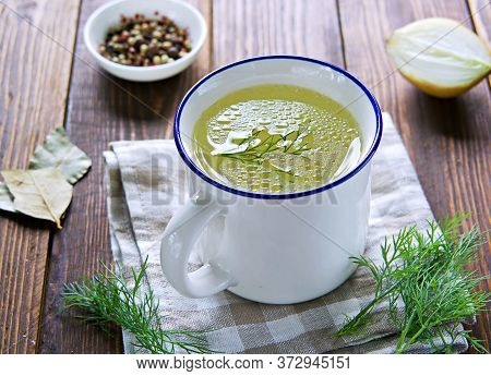 Chicken Or Meat Broth In A White Ceramic Mug With A Blue Rim On A Wooden Background. Broth Recipes.