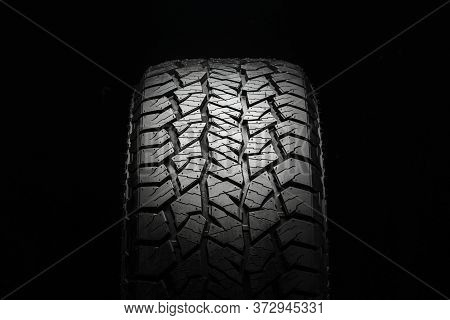Mud All-season All Terrain Tire With A Powerful Tread. Front View On A Black Background Close Up