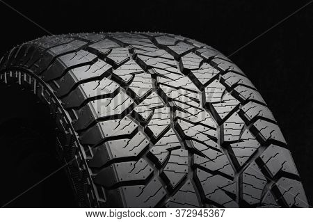 Mud All-season Tire With A Powerful Tread. Side View On A Black Background Close Up