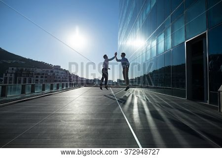 Male executives giving high five to each other in Male executives walking together in office premises