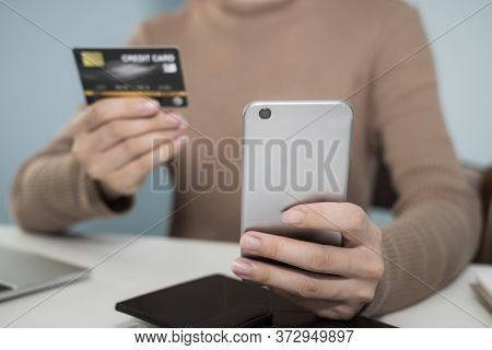 Young Woman Hand Using Digital Mobile Phone Scan And Payment Online With Credit Card On Desk In Home