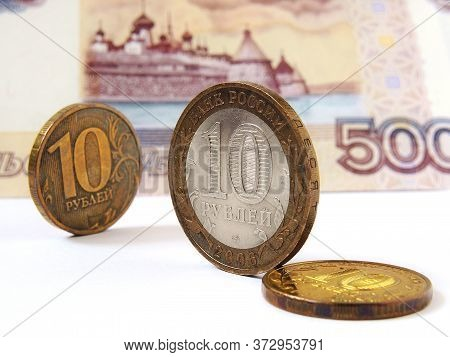 Russian Coins Of 10 Rubles Are On The Background Of A Banknote Of 500 Rubles. One Of The Coins Is Co