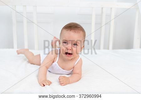 Baby Girl 6 Months Old Lying On The Bed In The Children's Room On Her Stomach And Crying, Baby Morni