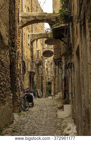 Narrow And Mysterious Road In A Mountain Town. Narrow Street With Houses And Walls Made Of Stone And