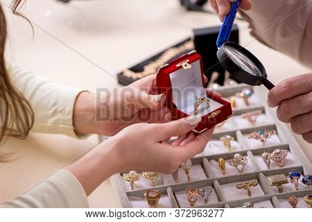Young woman visiting old male jeweler