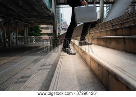 Businessman Carrying A Briefcase Walk Up Stair To Discuss Business At The Office Building With A Tal