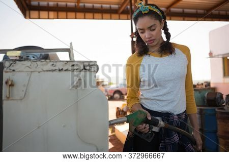 Woman filling petrol in car at petrol pump on a sunny day