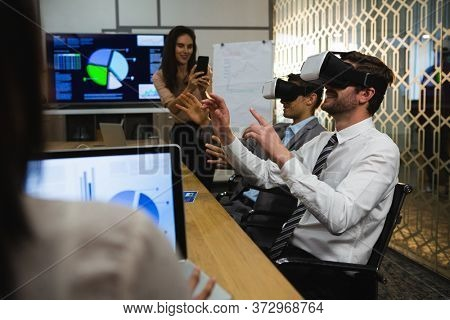 Businessmen using virtual reality headset in conference room at office