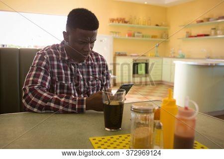 Tensed man using mobile phone in restaurant