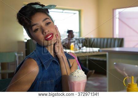 Thoughtful woman looking away while having milkshake in the restaurant