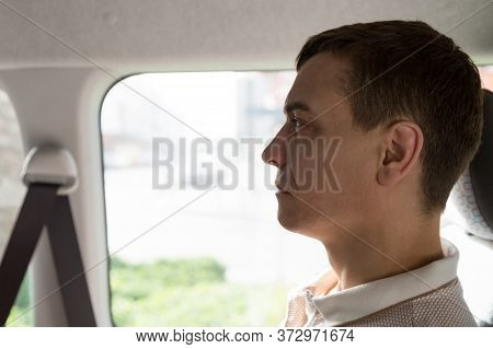 Passenger Public Transport In Europe. A 30-35 Year Old Man Sits In A Taxi Near The Window.