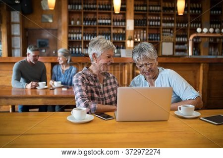 Senior female friends using laptop while couple having tea in background at restaurant