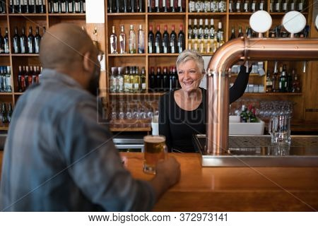 Man talking to senior waitress while having glass of beer at counter in bar