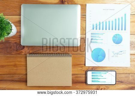 Top View Of A Wooden Desk Color With A Computer Graph, Magnifier And Office Business Calculator.