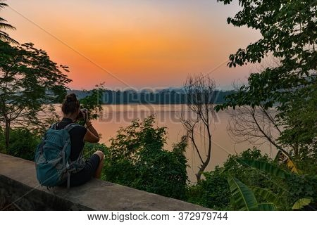 Woman Backpacker Takes Pictures Of Mekong River At Sunset Luang Prabang