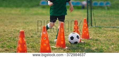 Child Running Soccer Ball Between Training Cones. European Football Sports Summer Camp For Junior Le