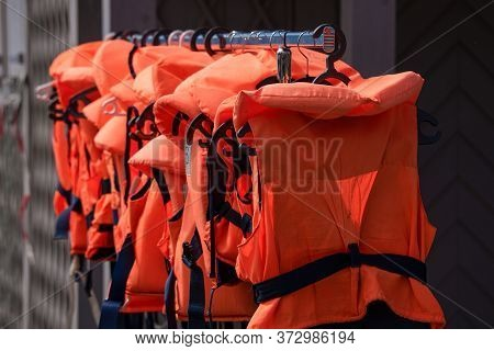 Orange And Black Lifejackets In A Row.