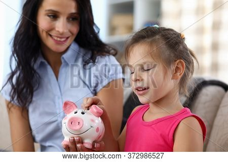 Smiling Little Girl Making Wish While Putting Silver Coin In Pink Funny Piggybank Slot Portrait