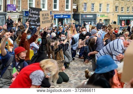 Richmond, North Yorkshire, Uk - June 14, 2020: Protesters Hold Homemade Anti Racism Signs While Knee