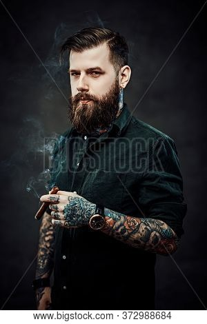 Stylish Bearded Man Smokes A Cigar. Studio Portrait Of A Handsome Tattooed Hipster Guy Who Smokes A