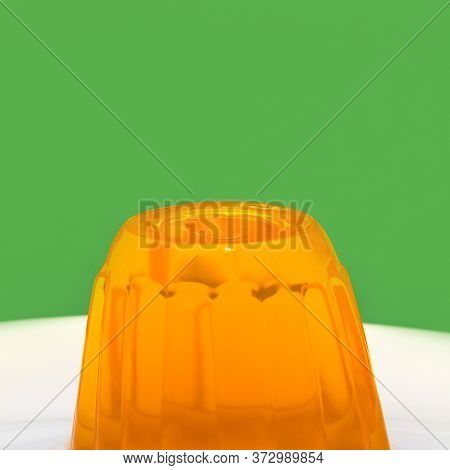 Close Up Of A Orange Gelatin On A White Plate. Green Background.