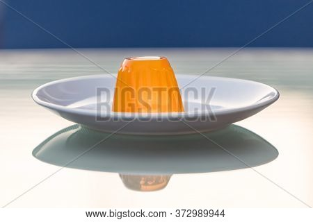 Close-up Of An Orange Gelatin On A White Plate Reflected On A Glass Table