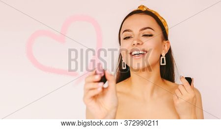Portrait Happy Stylish Attractive Girl Apply Lipgloss To Make Drawn Love Shape, Have Fun Isolated Wh
