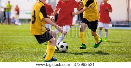 Junior Level Team Sports Competition. Group Of Young Boys Playing Soccer On The School Field