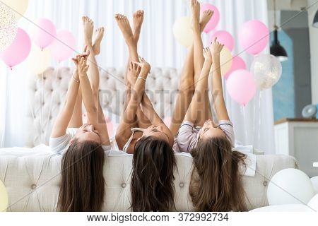 Charming Foolish Girls Lying Head Over Heels On Bed With Raised Crossed Legs Hands Celebrating Birth