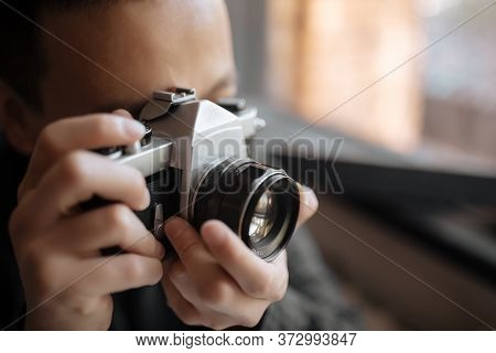 Man Taking A Picture On A Pentax Film Camera Against A Window
