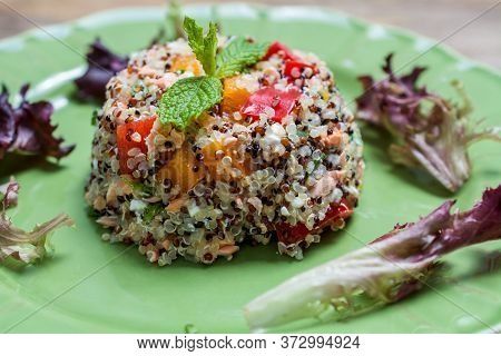 Closeup On Green Plate With Tri-color Quinoa Salad On Wooden Table - Quinoa Is A Pseudograin That Ha