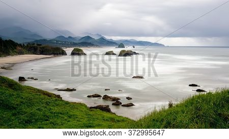 Long Exposure Of Cannon Beach In Oregon, Usa Featuring Rocky Outcrops In The Ocean And Mountains In