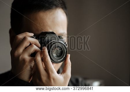 Man Taking A Picture On A Pentax Film Camera. Close Up. Black Background