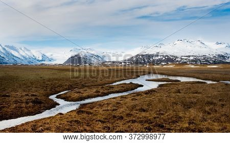 Typical Icelandic Dramatic Landscape With Frozen Lake And Mountains Covered In Snow In Iceland